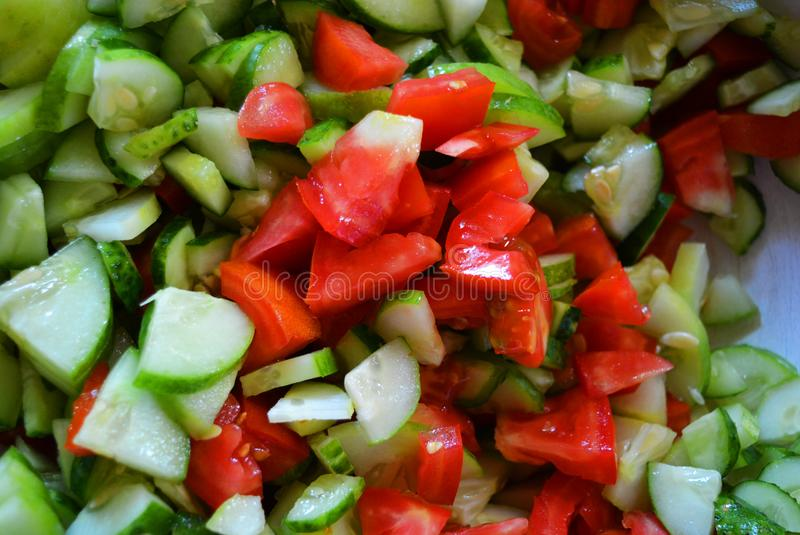 Fresh healthy vegetables, small slices of green cucumbers and red tomatoes for summer salad, ingredients for salad. stock images