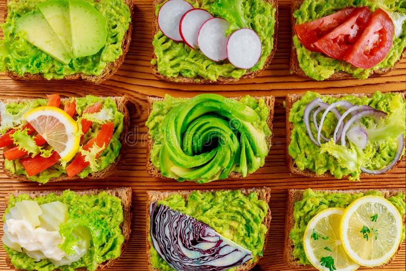 Fresh avocado toasts with different toppings, healthy vegetarian breakfast with wholegrain sandwiches royalty free stock images