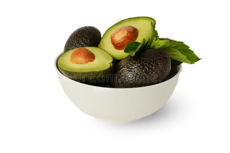 Fresh Healthy Whole and Half Hass Avocados with Basil Leafs Covered in Lemon Juice in a White Bowl on Clean White Background royalty free stock photography
