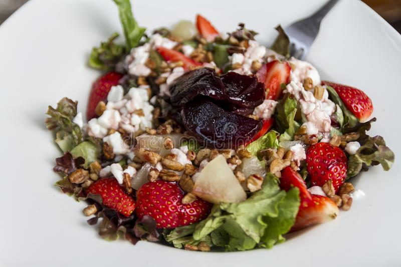Delicious fresh and sweet salad with strawberries, nuts and cheese royalty free stock image