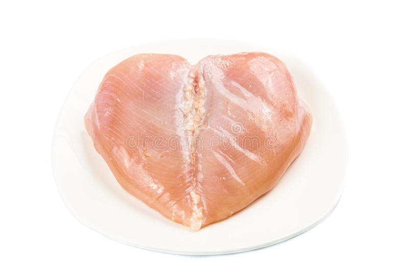 Fresh heart shaped skinless chicken breast meat on a plate.  royalty free stock images
