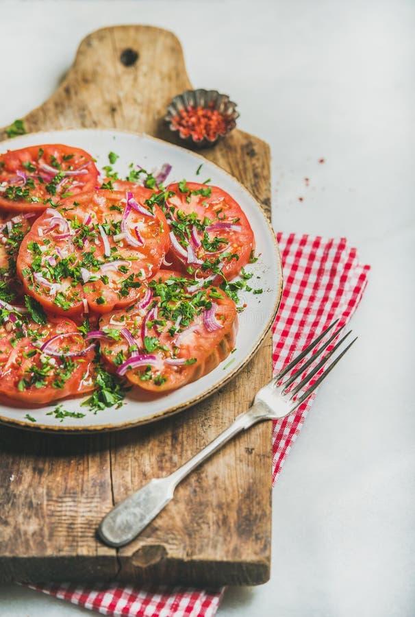Fresh heirloom tomato, parsley and onion salad. Vegan food concept stock image