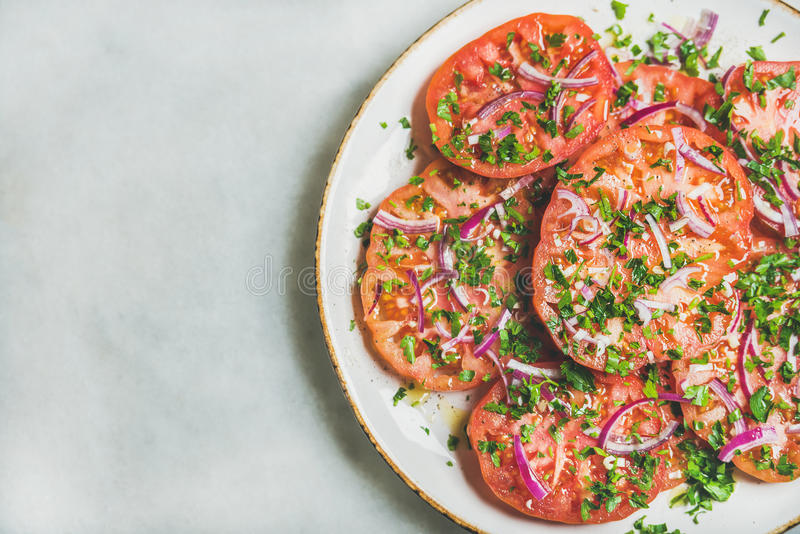 Fresh heirloom tomato, parsley and onion salad in white plate stock images