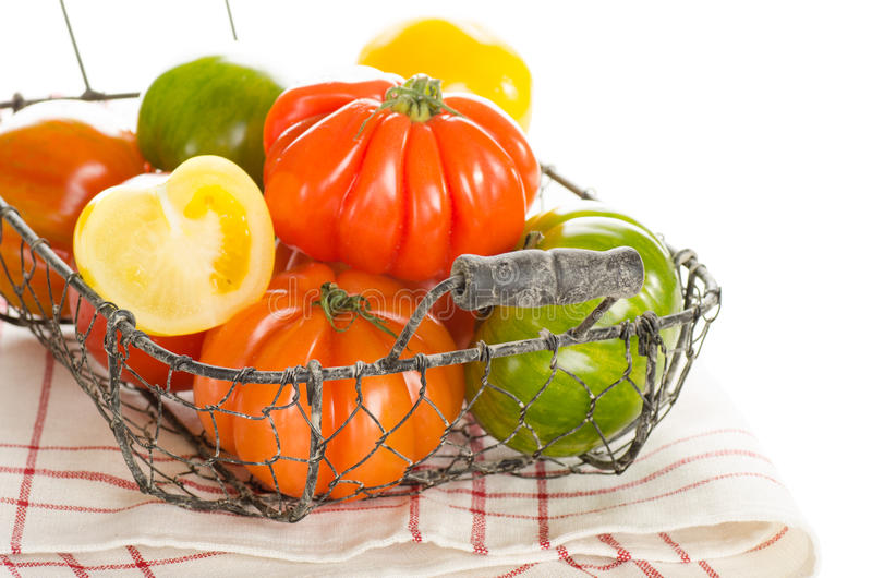 Fresh heirloom tomatoes in a basket. Isolated on white royalty free stock photo