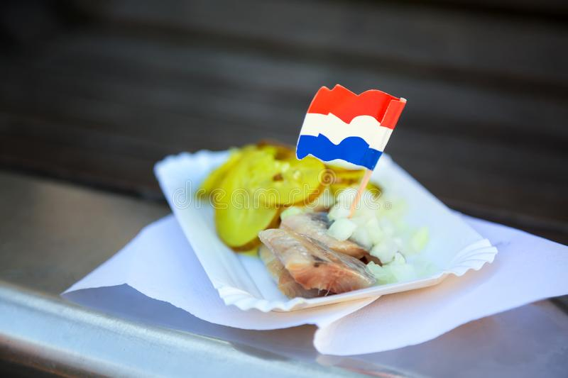 Fresh herring with onion, pickled cucumber pieces and Netherlands flag close up. Traditional Amsterdam street food.  royalty free stock photo