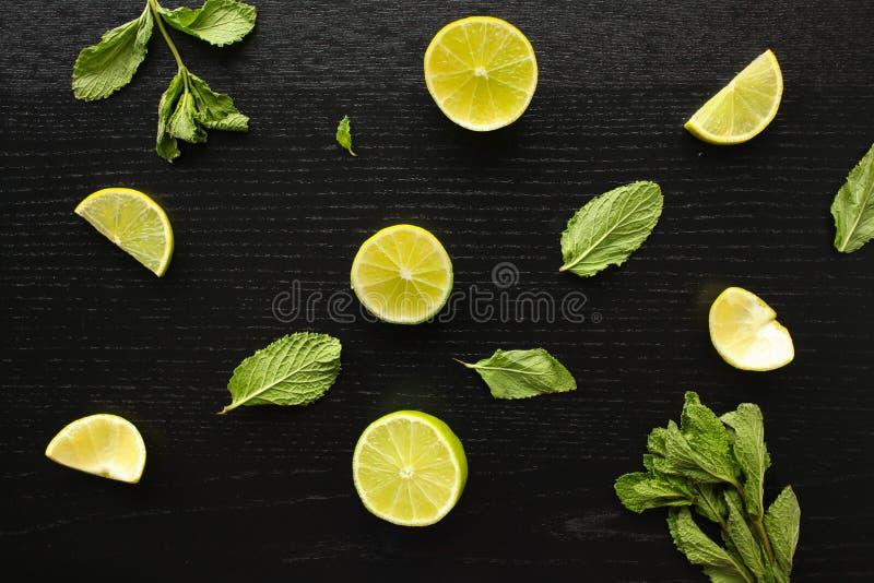 Fresh home-made lemonade ingredients: lemon, lime and mint on black background stock images