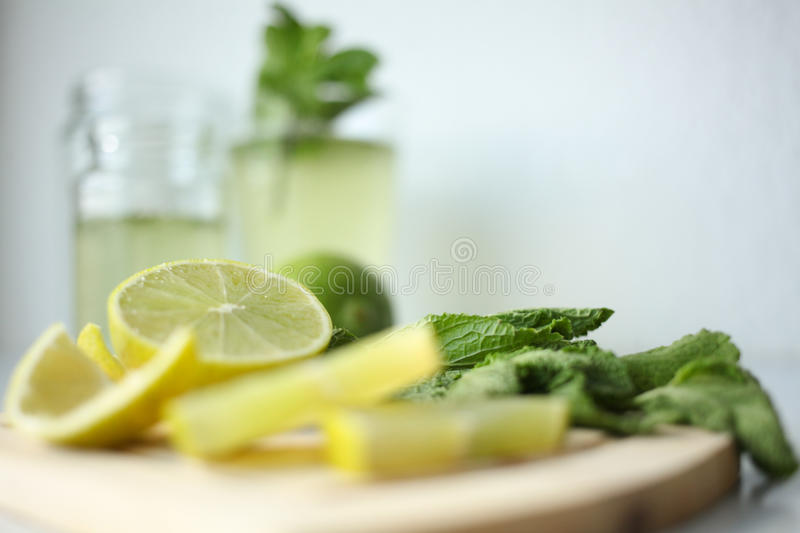 Fresh home-made lemonade ingredients: lemon, lime and mint, a glass on white background stock photo