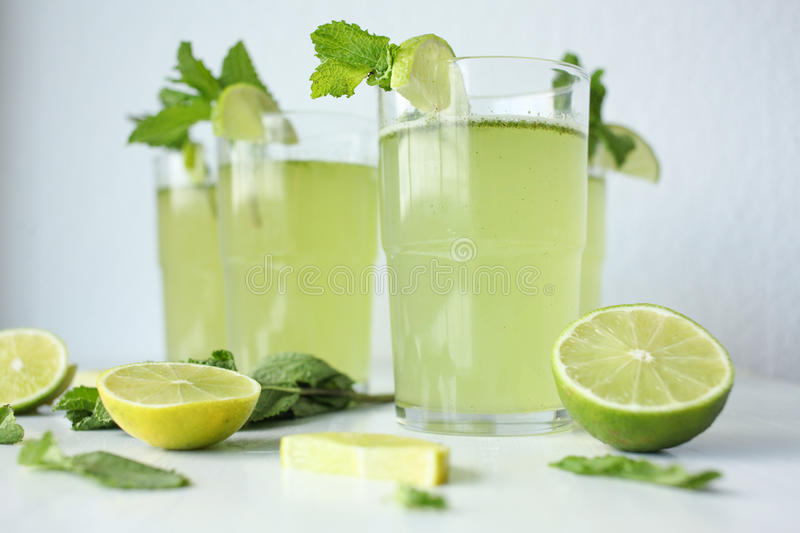 Fresh home-made lemonade with lemon, lime and mint in a glass on white background and ingredients laying on the table royalty free stock photo