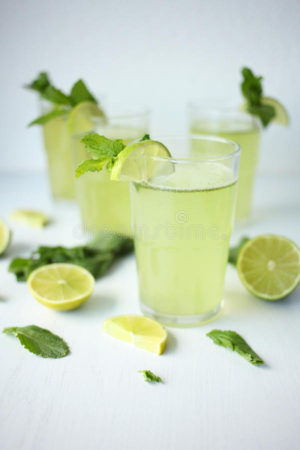 Fresh home-made lemonade with lemon, lime and mint in a glass on white background and ingredients laying on the table royalty free stock photography
