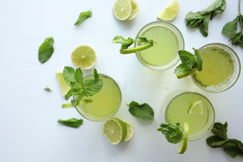 Fresh home-made lemonade with lemon, lime and mint in a glass on white background and ingredients laying on the table royalty free stock image