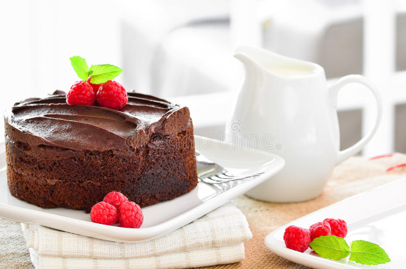 Fresh home made sticky chocolate fudge cake with raspberries royalty free stock photography