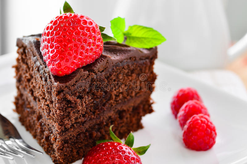 Fresh home made sticky chocolate fudge cake with strawberries and raspberries stock images