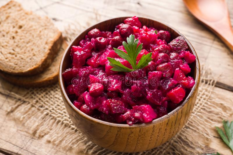 Fresh homemade beet salad vinaigrette in a wooden bowl. Traditional Russian food.  stock photos