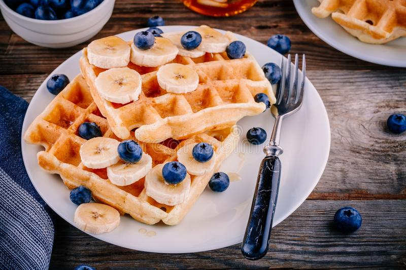 Fresh homemade belgian waffles with blueberries and banana for breakfast royalty free stock photo