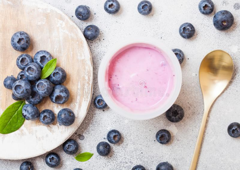 Fresh homemade blueberry yogurt with fresh berries on wooden board and golden spoon stock images