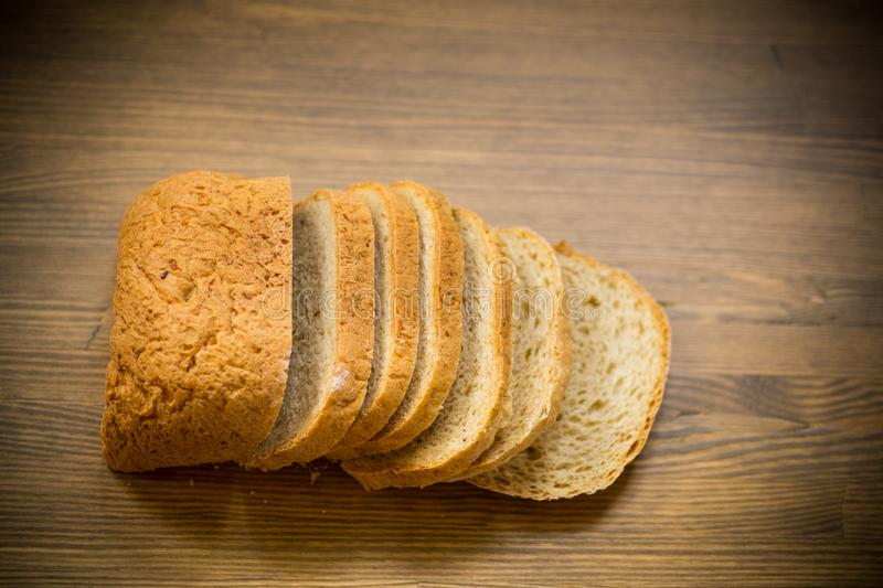 Fresh homemade bread sliced on wooden background royalty free stock photography