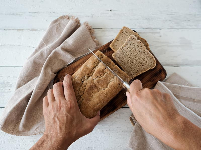 Fresh homemade bread. Women`s hands cut bread. Bread is located on a wooden surface. Near napkins. White wood background. Top vie. W. The concept for baking stock photography