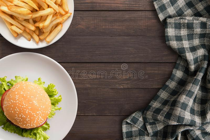 Fresh homemade burger and french fries on wooden table. Top view, Copy space. stock photography