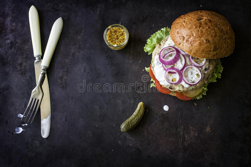 Fresh homemade burger with spicy sauce,cornichons and herbs over dark metal background royalty free stock photo