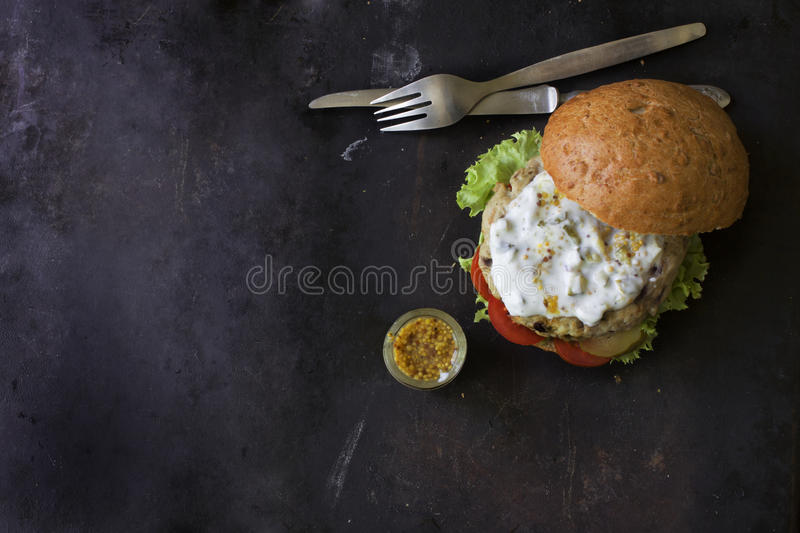 Fresh homemade burger with spicy sauce,cornichons and herbs over dark metal background stock photos