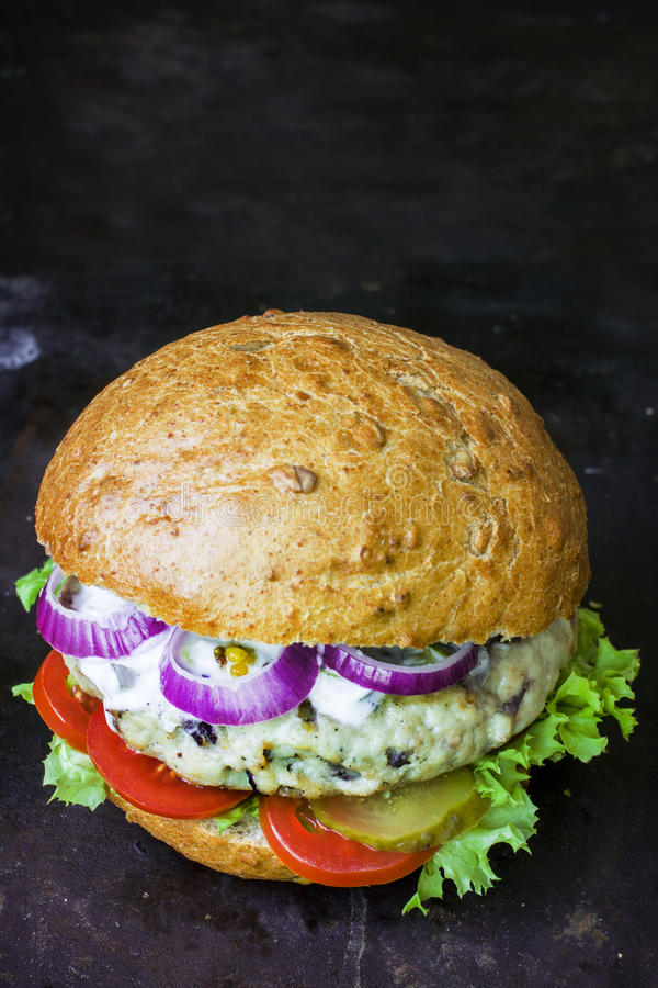 Fresh homemade burger with spicy sauce,cornichons and herbs over dark metal background stock photo