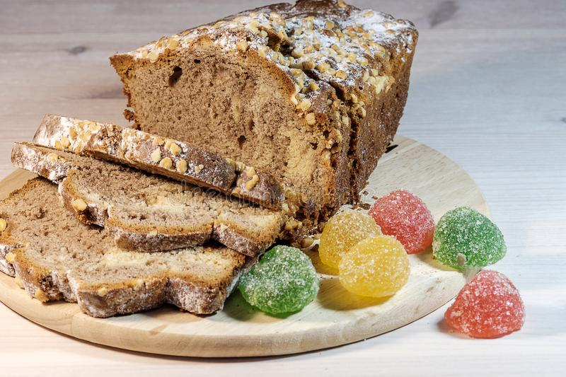 Fresh homemade cake dusted with powdered sugar and multi-colored marmalade royalty free stock image