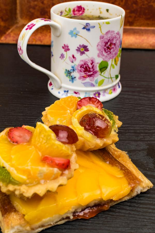 fresh homemade cakes with fruit, apricot, grape, orange, kiwi and tea cup on red decoration plate. Desserts. Sweet life stock photo