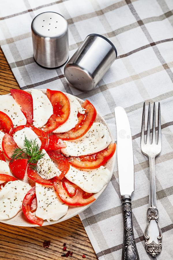 Fresh homemade Caprese salad served on white textile. Italian cuisine top view with copy space. Healthy, dieting food for lunch. royalty free stock photography