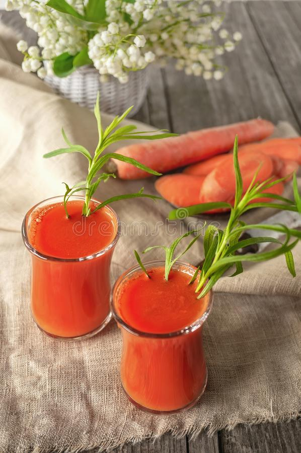 Fresh homemade carrot juice into two glass cups. With carrot and white flowers royalty free stock image