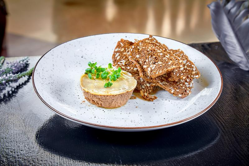 Fresh homemade chicken or duck liver pate with bread, croutons on white plate. Dark background. Copy space, horizontal. Restaurant stock photography