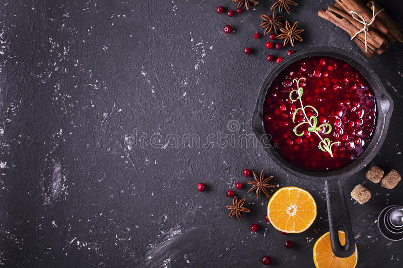 Fresh homemade cranberry sauce in a pan on dark wooden background with scattering of ripe berries. royalty free stock images
