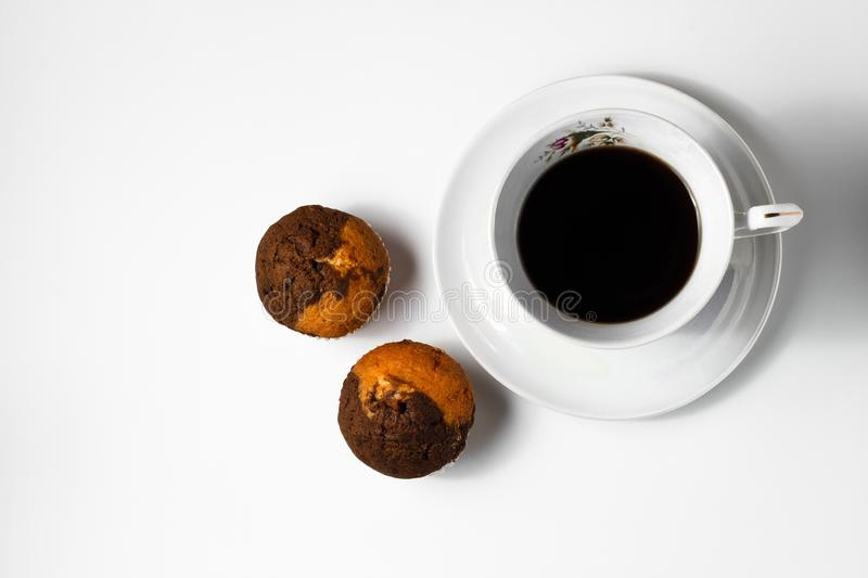 Fresh homemade cupcakes with a cup of coffee on a white background. View from above. stock image