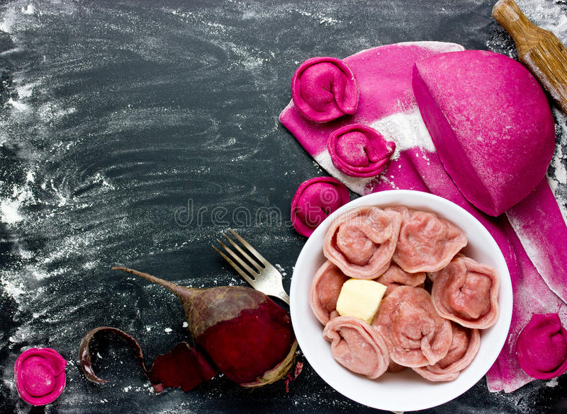 Fresh homemade dough with beetroot juice and pink dumplings stuffed with meat on a black background with ingredients. Making royalty free stock photography