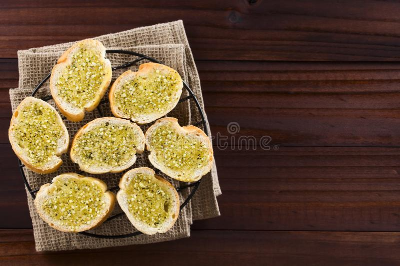 Fresh Garlic Bread with Oregano. Fresh homemade garlic bread, slices of baguette seasoned with garlic, oregano, salt, pepper and olive oil, photographed overhead royalty free stock image