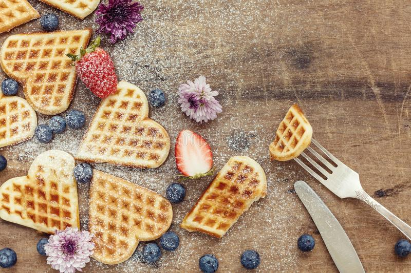 Fresh homemade heart shape waffles with blueberries and strawberry on wooden background, top view royalty free stock photos