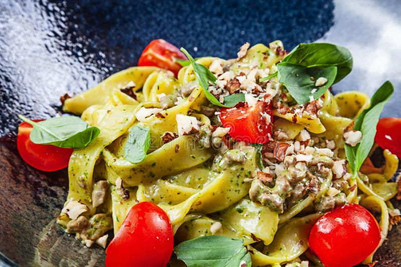 Fresh homemade italian pasta with tomatoes, basil and veal, parmesan. CLose up view selective focus. Italian cuisine. Food with royalty free stock photography