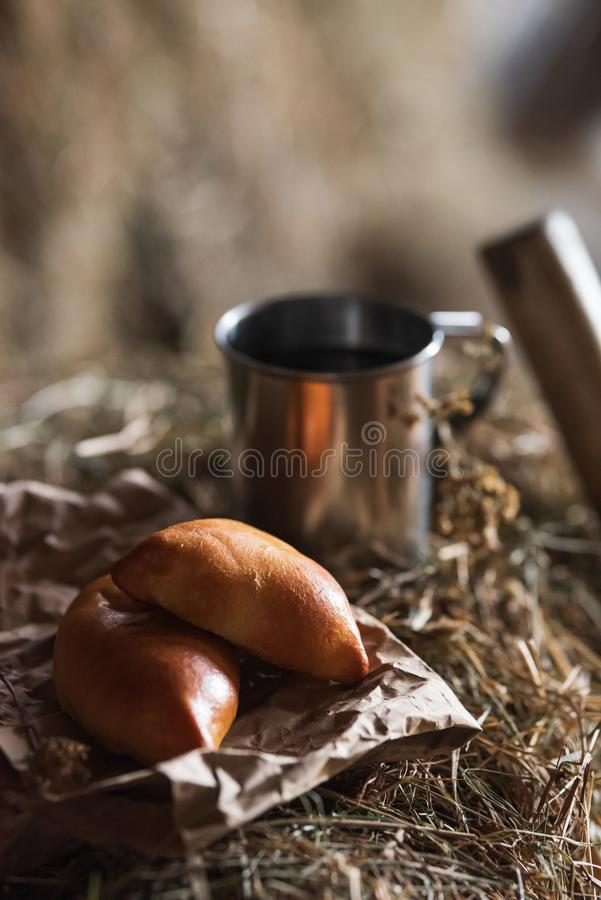 Fresh homemade meat patty cakes and steel cup on hayloft stock image