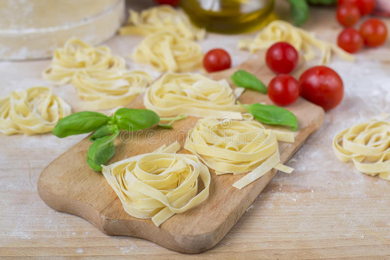 Fresh homemade pasta machine pasta, basil,. tomatoes on a wooden royalty free stock image