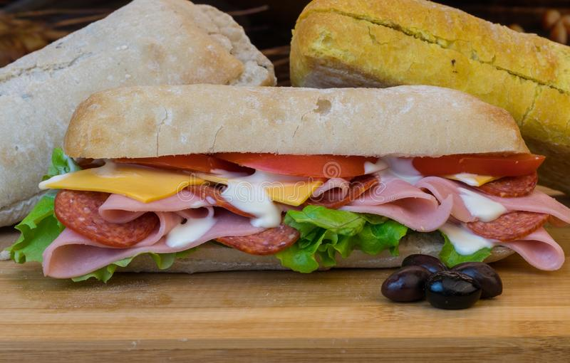 Fresh Homemade Sandwich with ham, pepperoni, fresh tomatoes, lettuce, olives and cheddar cheese royalty free stock photo