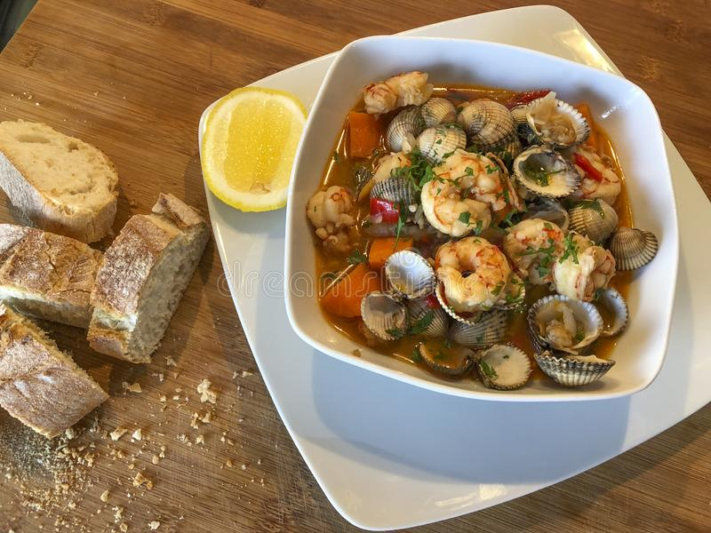 Fresh homemade seafood stew casserole. Fresh homemade seafood stew prepared in a casserole with bread stock images