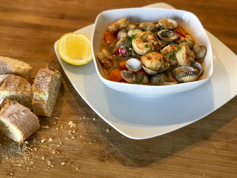 Fresh homemade seafood stew casserole. Fresh homemade seafood stew prepared in a casserole with bread stock photo