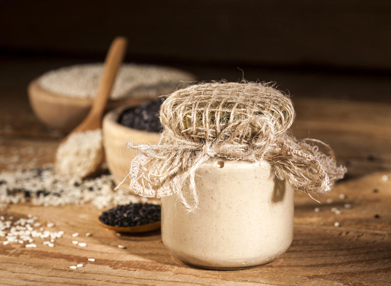 Fresh homemade sesame tahini in a glass jar and seeds in wooden bowls and spoons royalty free stock photo