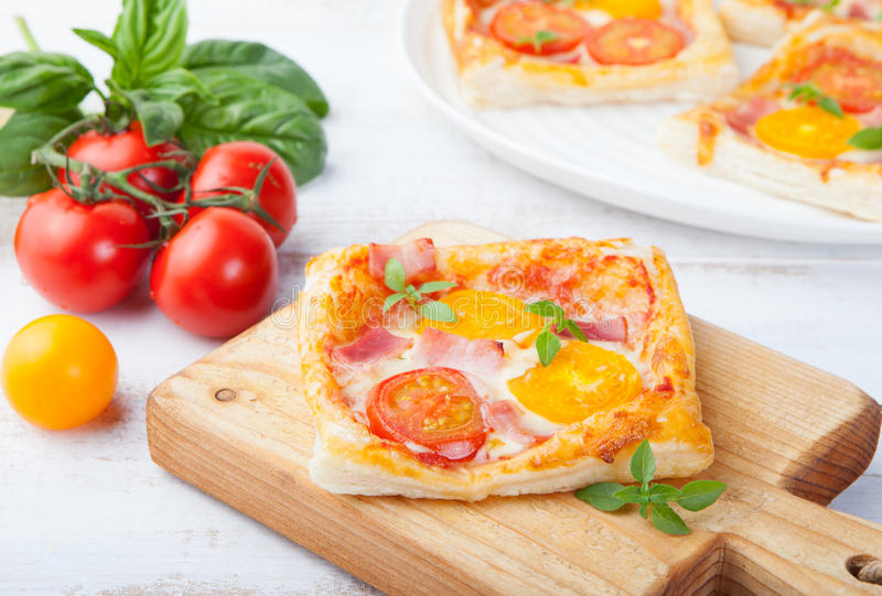 Fresh homemade square Pizza with vegetables and basil on cutting board stock photo
