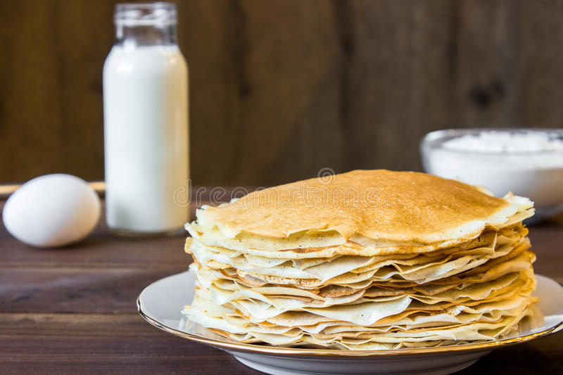 Fresh homemade stack of crepes with ingredients. On wooden background royalty free stock images
