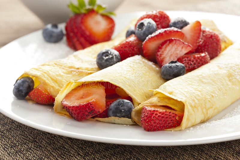 Fresh Homemade Strawberry Crepes. Fresh Homemade Rolled Strawberry Crepes with blueberries stock image