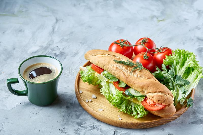 Fresh sandwich with lettuce, tomatoes, cheese on wooden plate, cup of coffee on white background, selective focus stock photography