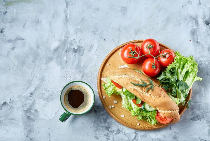 Fresh sandwich with lettuce, tomatoes, cheese on wooden plate, cup of coffee on white background, selective focus royalty free stock photos