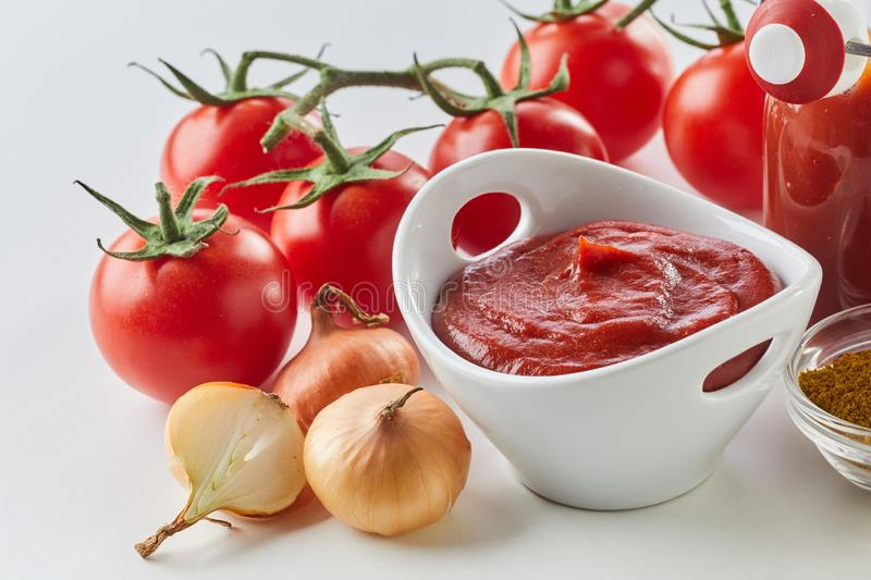 Fresh homemade tomato sauce with ingredients. Fresh homemade tomato sauce in a bowl surrounded with ingredients in a close up wide angle view stock photos