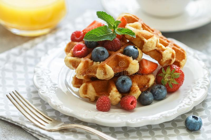 Fresh homemade waffles with raspberries, strawberries, blueberries and honey royalty free stock images