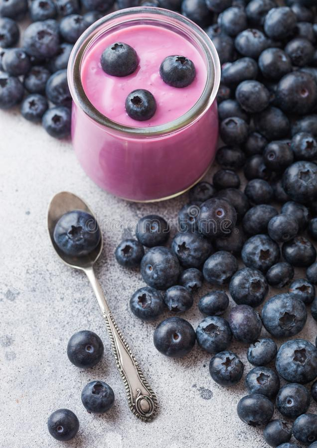 Fresh hommemade creamy blueberry yoghurt with fresh blueberries and silver spoon on stone kitchen table background. Fresh homemade creamy blueberry yoghurt with royalty free stock photos